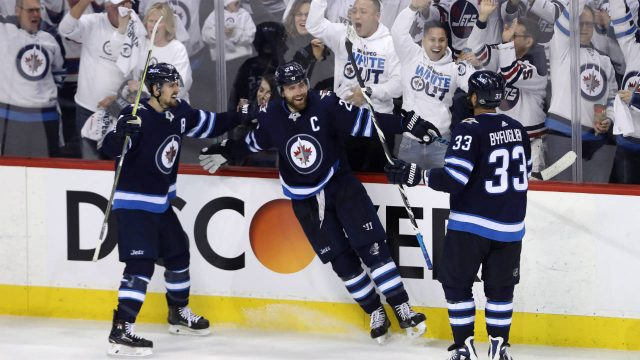 Winnipeg-Jets'-Mark-Scheifele-(55),-Blake-Wheeler-(26)-and-Dustin-Byfuglien-(33)-celebrate-after-Wheelers-scored-against-the-Nashville-Predators-during-third-period-NHL-hockey-playoff-action-in-Winnipeg,-Tuesday,-May-1,-2018.-(Trevor-Hagan/CP)