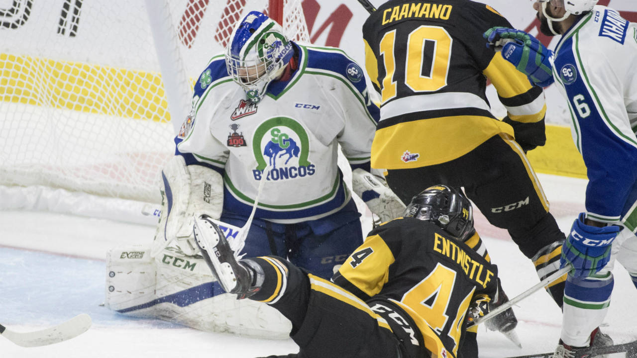 Swift-Current-Broncos-defenceman-Sahvan-Khaira-(6)-looks-on-as-Hamilton-Bulldogs-forward-MacKenzie-Entwistle-(44)-and-Hamilton-Bulldogs-forward-Nicholas-Caamano-(10)-tries-to-get-a-shot-past-Swift-Current-Broncos-goalie-Stuart-Skinner-(74)-during-first-period-Memorial-Cup-action-in-Regina-on-Monday,-May-21,-2018.-(Jonathan-Hayward/CP