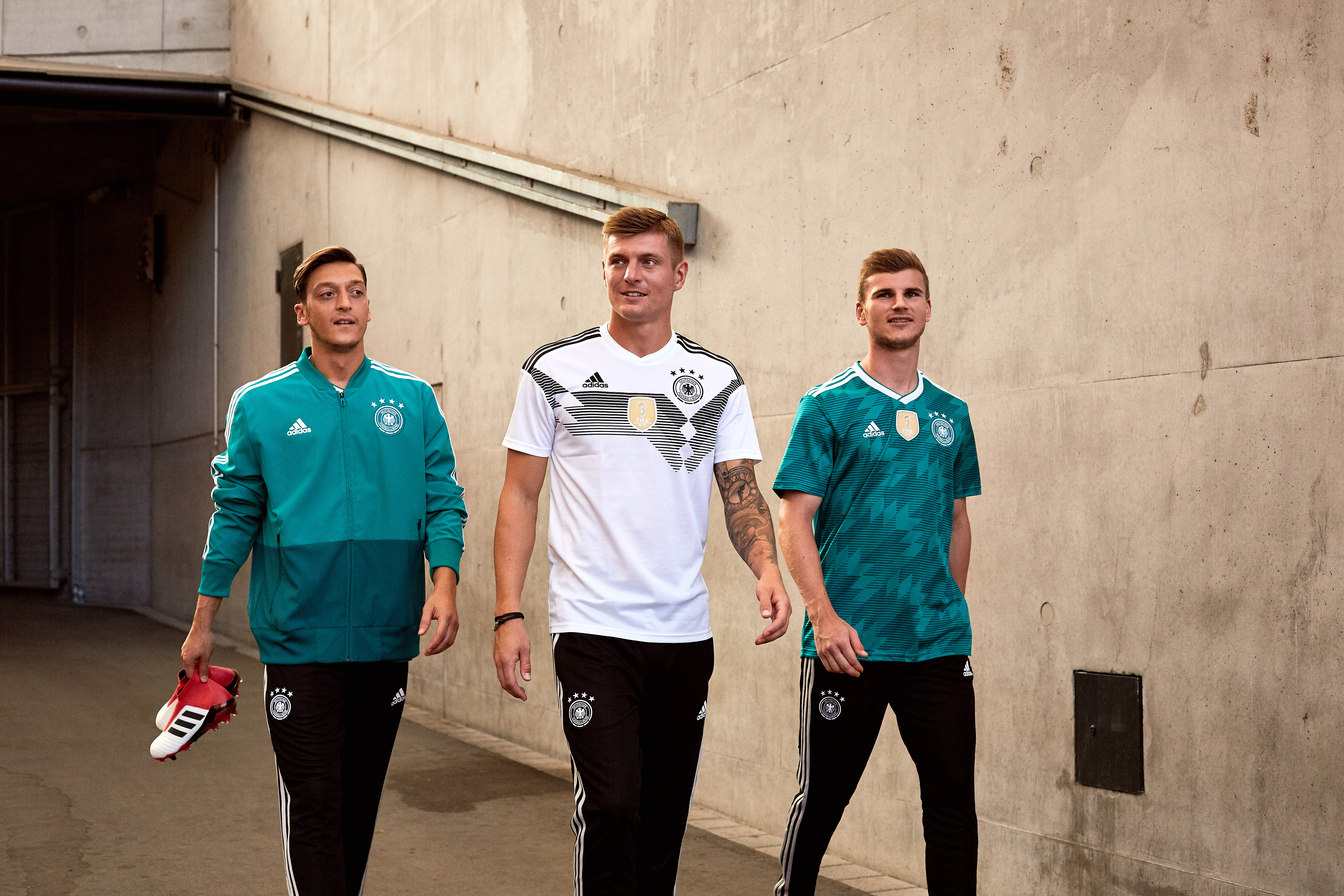 """12eba3766 The collar has the words """"Die Mannschaft,"""" which means """"The Team"""" on the  neckline. A gold World Cup winner badge is on the front of the jersey."""