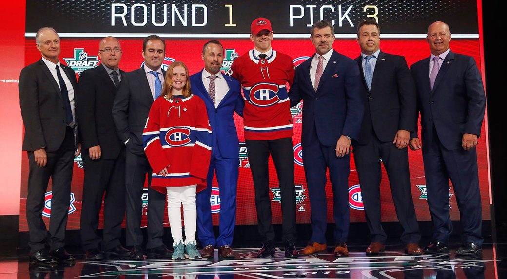 Jesperi-Kotkaniemi,-centre,-of-Finland,-stands-on-stage-after-being-selected-by-the-Montreal-Canadiens