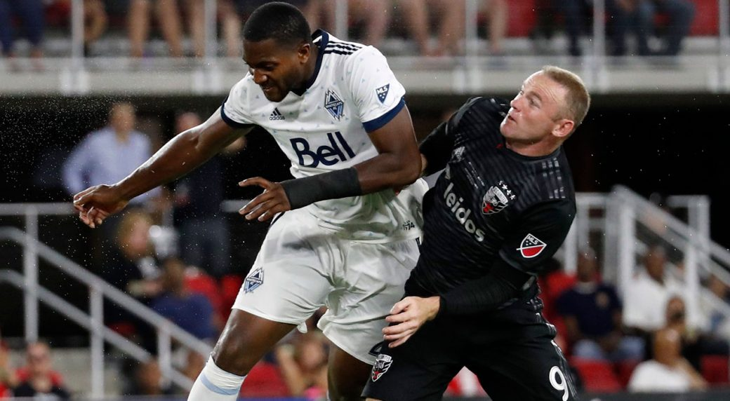 wayne_rooney_competes_for_a_header_with_doneil_henry
