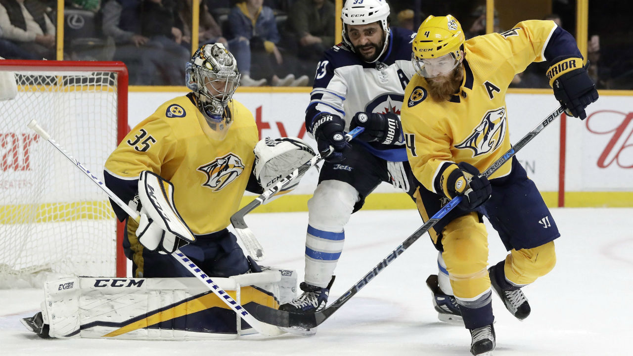 Winnipeg-Jets'-Dustin-Byfuglien-and-Nashville-Predators'-Ryan-Ellis-chase-a-rebound-after-Predators-goalie-Pekka-Rinne-blocked-a-shot-in-an-NHL-hockey-game