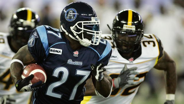 ricky-williams-runs-the-ball-against-the-tiger-cats