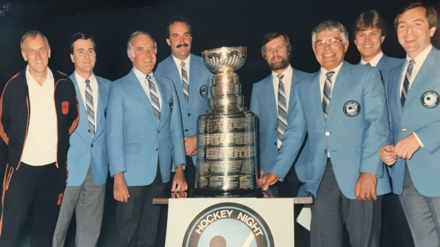 (Left-to-right):-Ralph-Mellanby,-then-executive-producer,-HNIC,-host-Chris-Cuthbert,-play-by-play-man-Don-Wittman,-colour-analyst-John-Davidson,-director-Larry-Brown,-analyst-Howie-Meeker,-associate-producer-Steve-Lansky-and-John-Shannon-at-the-1985-Stanley-Cup-Final-in-Edmonton.