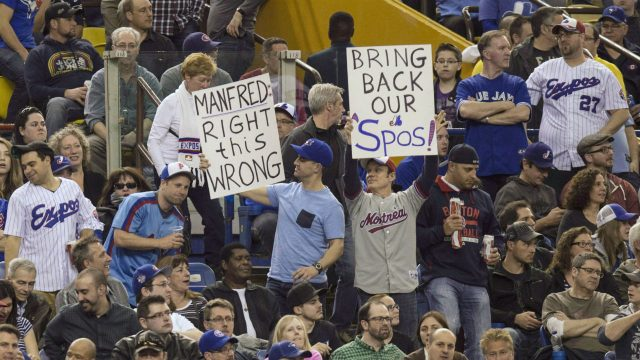 Fans-hold-up-signs-as-the-Toronto-Blue-Jays-face-the-Cincinnati-Reds-in-Grapefruit-League-play-on-April-3,-2015-in-Montreal.