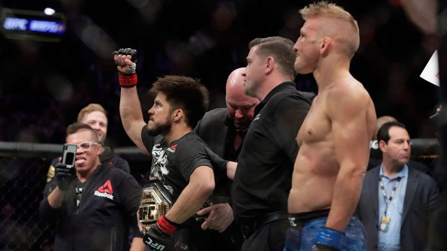 tj-dillashaw-looks-on-as-henry-cejudo-has-ufc-belt-wrapped-around-waist