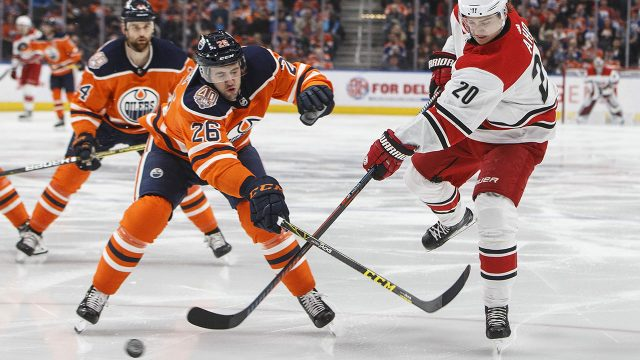 sebastian-aho-battles-brandon-manning-for-the-puck