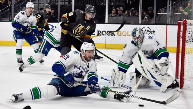 alexander-edler-and-jakob-markstrom-defend-against-the-golden-knights