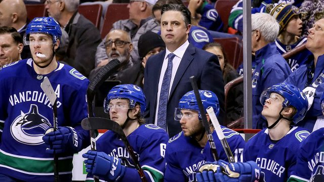 NHL-Canucks-Green-stands-behind-bench-during-game