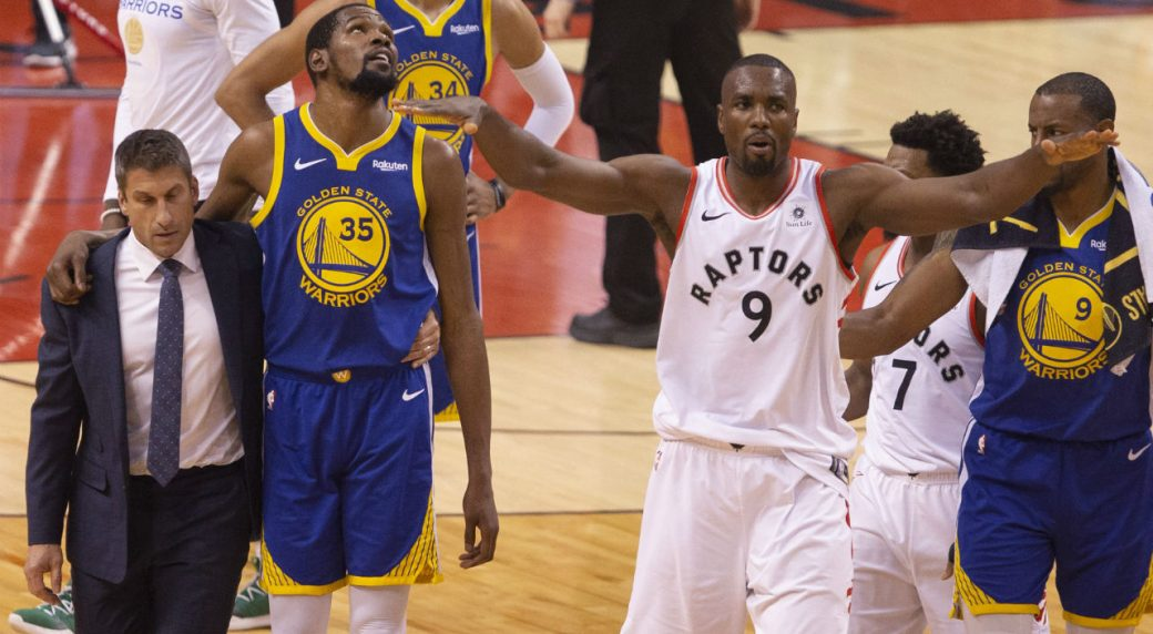 Golden-State-Warriors-forward-Kevin-Durant-(35)-walks-off-the-court-after-sustaining-an-injury-as-Toronto-Raptors-centre-Serge-Ibaka-(9)-gestures-to-the-crowd-during-first-half-basketball-action-in-Game-5-of-the-NBA-Finals-in-Toronto-on-Monday,-June-10,-2019.-(Chris-Young/CP)