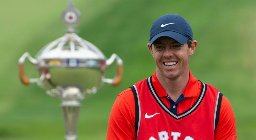 Rory-McIlroy-laughs-as-he-puts-on-a-Toronto-Raptors-jersey-during-the-trophy-presentation-at-the-Canadian-Open-golf-championship