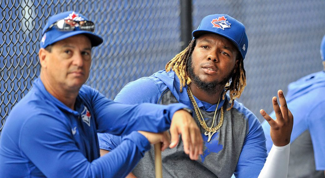 Toronto-Blue-Jays-manager-Charlie-Montoyo,-left,-and-infielder-Vladimir-Guerrero-Jr.-sit-outside-the-batting-cages