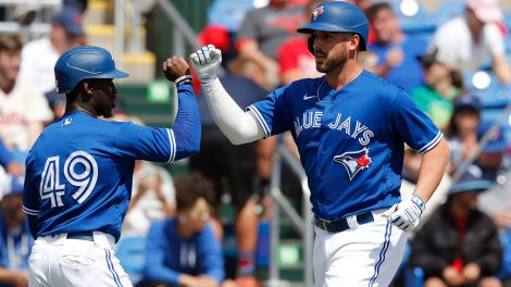 Toronto-Blue-Jays'-Travis-Shaw,-right,-is-greeted-at-home-after-his-two-run-home-run-during-a-spring-training-baseball-game-against-the-Philadelphia-Phillies