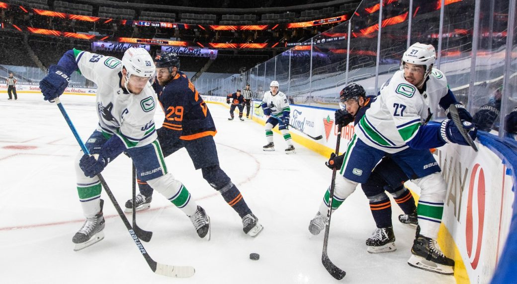 Missing in action. Canucks' Miller sits and waits as the Oilers outgun Vancouver and split the opening series